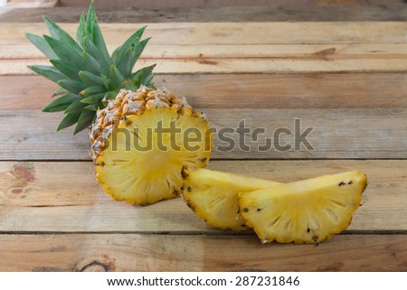 Pineapple slices on wood table - stock photo