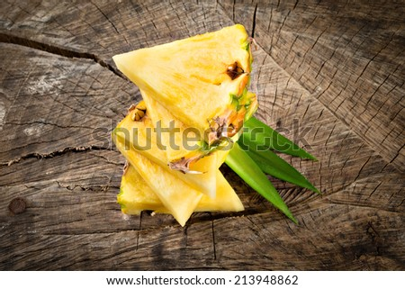 Pineapple slices on wooden background - stock photo