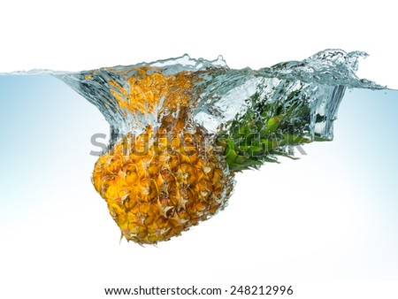 pineapple splashes into the water - stock photo