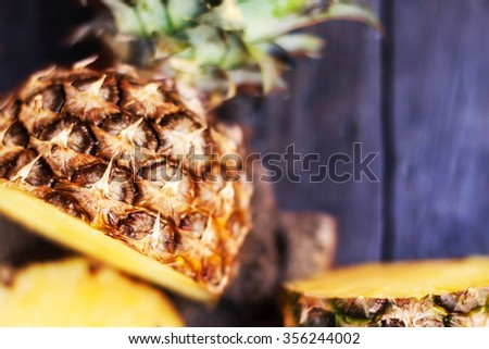 Pineapple tropical fruit or ananas with circle slices over wooden background  - stock photo