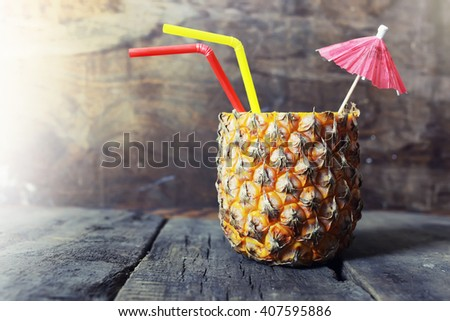 pineapple with straw and cocktail umbrella - stock photo