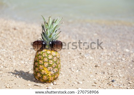 Pineapple with sunglasses on the beach  - stock photo