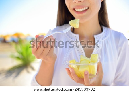 Pineapple - woman eating sliced Hawaiian pineapple fruit as a healthy snack from take away bowl. - stock photo