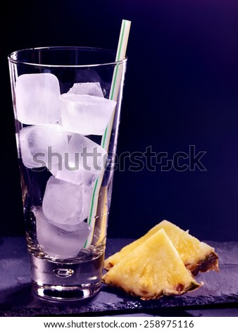 Pineapplee drink on black background. Empty glass with ice cube . - stock photo