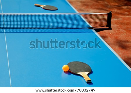 Ping pong ball with paddle on tennis table - stock photo