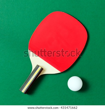 Ping pong paddle with a white ball on green table