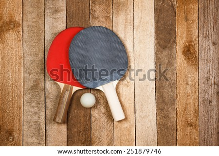Ping pong paddles and ball on retro wooden background - stock photo