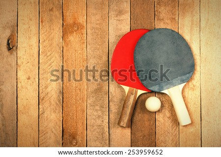 Ping pong paddles and ball on wooden texture with copyspace - stock photo