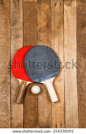 Ping pong paddles with ball on vintage wooden background - stock photo