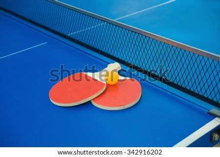 pingpong rackets and ball and net on a blue pingpong table - stock photo