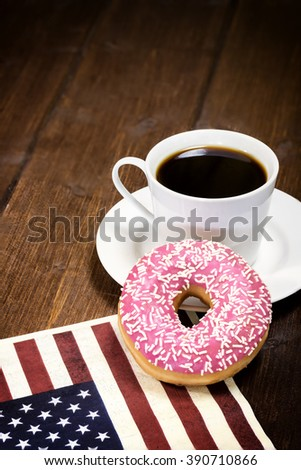 Pink american donut is leaning on a coffee cup lying on a napkin  with the design of the American flag.  Photo is designed as a vintage with dark edges. Vertically.  - stock photo