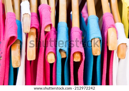 Pink and blue casual children's tops hanging - stock photo