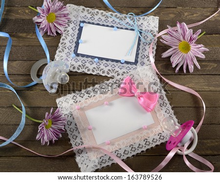 Pink and blue greeting cards with pacifiers and flowers on wooden background - stock photo