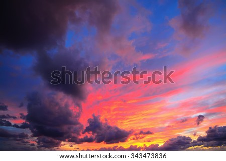 pink and blue sky with dark clouds at sunset - stock photo