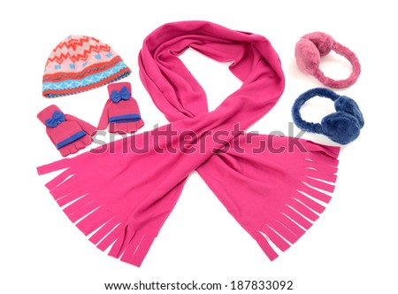Pink and blue winter accessories isolated on white background. Pink wool scarf, a pair of gloves,a hat and earmuffs nicely arranged and matching. - stock photo