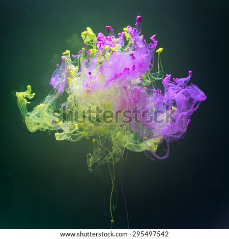 Pink and green complementary colors in fantastic shape. Colorful ink and paint spreading  underwater on dark green background. - stock photo