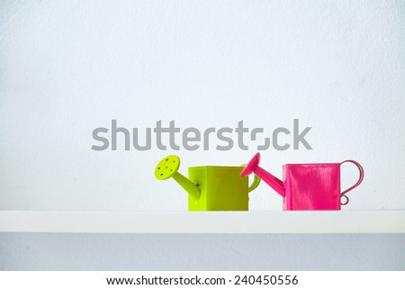 Pink and green watering pot on white background - stock photo
