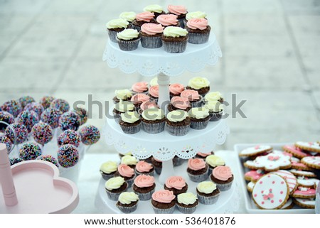 Pink and pale colors cup cakes, lolly pops, mousse for candy bar