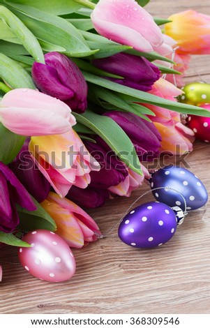 pink and purple easter tulips  with easter eggs on wooden table  - stock photo