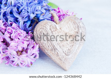 Pink and purple hyacinths with a wooden heart on a white table