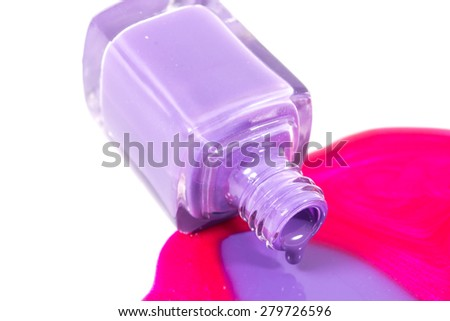 Pink and purple nail polishes pouring on the white background - stock photo