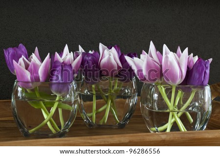 Pink and purple tulips in a vase on a wooden tray