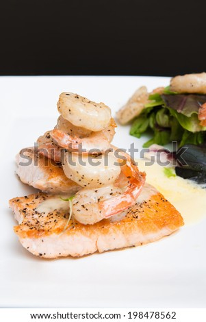 Pink and red shirimp and salmon presented on a white plate fine dining gourmet chef style - stock photo