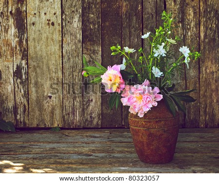 Pink and white flowers in a rustic vase on a grunge wood backdrop with copy space.