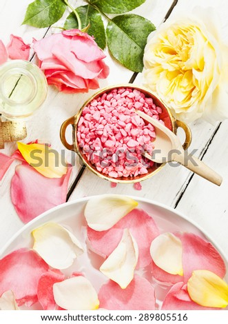 pink and yellow roses, petals, bath salt aromatic essence, top view, wood background - stock photo