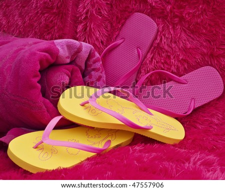 Pink and yellow summer thongs with beach towel - stock photo