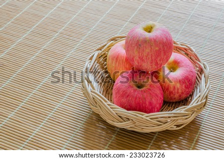 Pink Apples in the basket on the wood mat