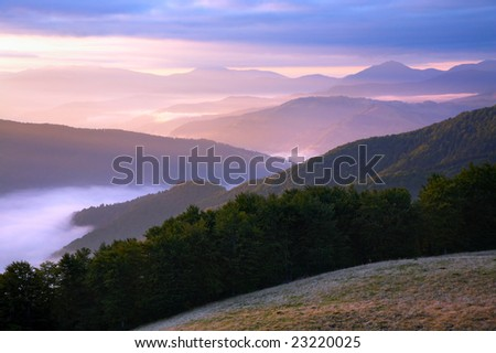 Pink autumn morning mountain view with sunbeam and haze - stock photo