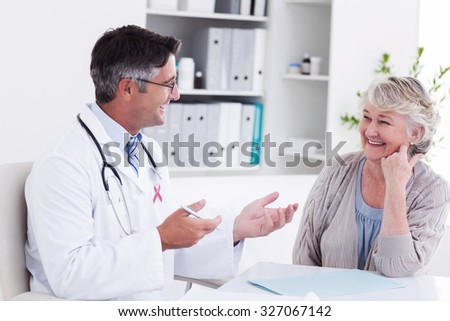 Pink awareness ribbon against doctor discussing with senior patient at table - stock photo