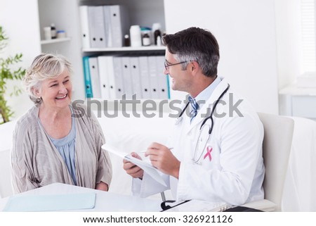 Pink awareness ribbon against doctor writing prescriptions for senior female patient - stock photo