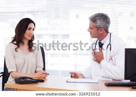Pink awareness ribbon against serious patient talking with her doctor about illness - stock photo