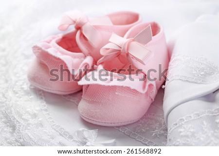 Pink baby boots on cloth close-up