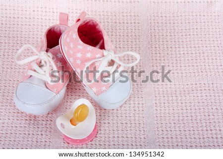 Pink baby shoes and dummy on pink background - stock photo