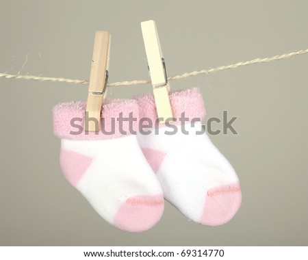 pink baby sock hanging on the clothesline - stock photo