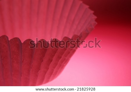 pink baking cup against a pink background - stock photo