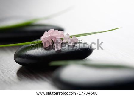 Pink bath salt on black stone - stock photo
