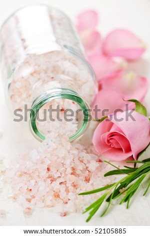 Pink bath salts in a glass jar with flowers and herbs - stock photo