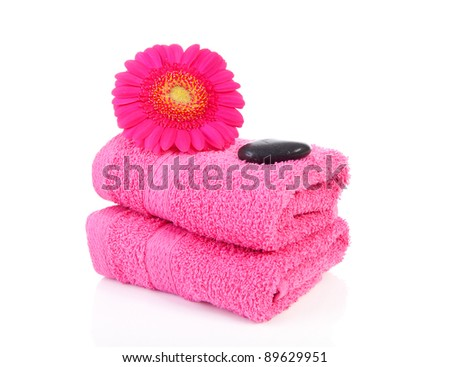 Pink bathroom accessories with towel, stones and Gerber flower over white background