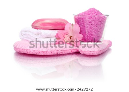 pink bathroom composition with scrubbing glove, bath salt, soap, towel and flower (with reflexion)