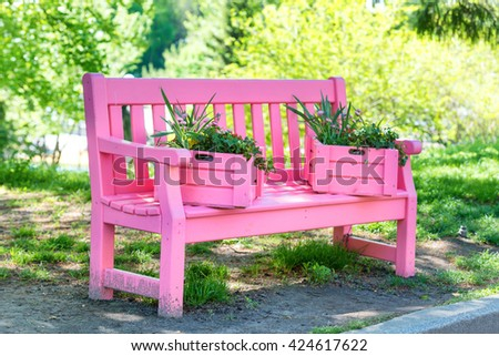 Pink bench with flowers in the green spring park