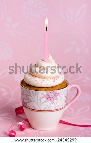 Pink birthday cupcake in a teacup - stock photo
