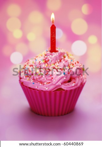 Pink birthday cupcake with a candle - stock photo