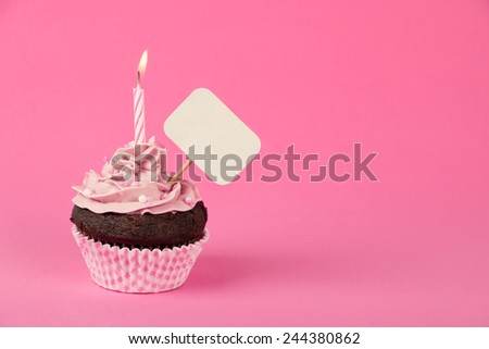 Pink birthday cupcake with a candle and blank placard - stock photo
