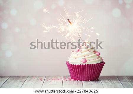 Pink birthday cupcake with sparkler - stock photo