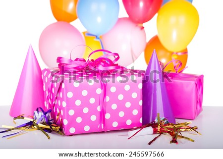 Pink birthday gift with party decorations - stock photo