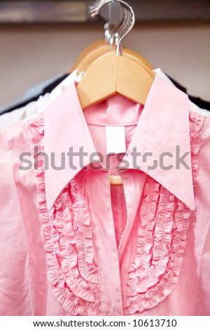 pink blouse hanging in a retail store - stock photo